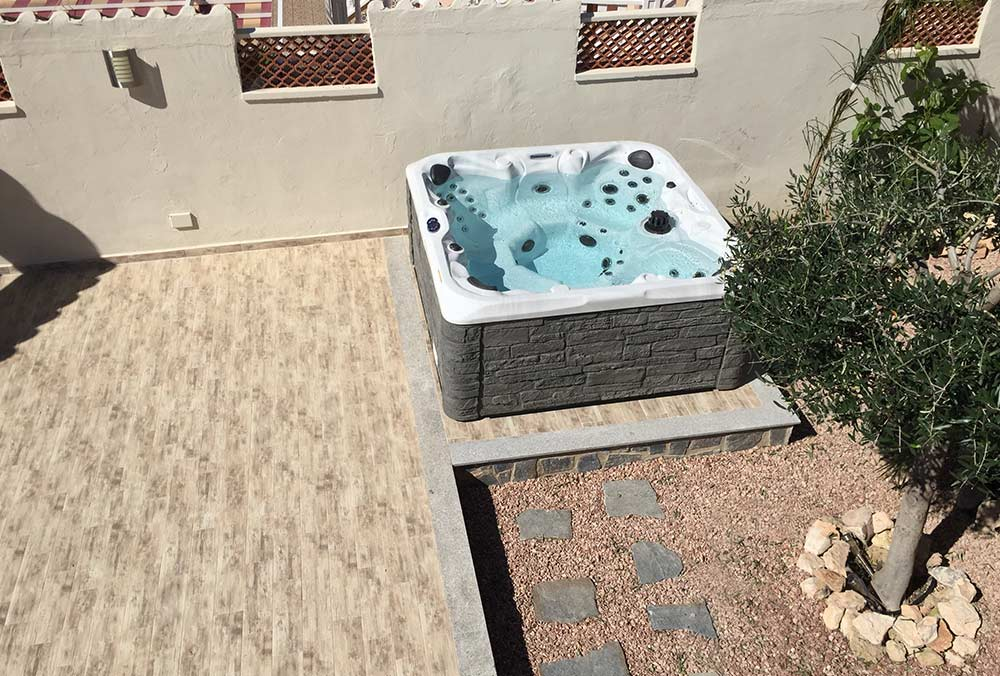 Hot tub with stone skirt on patio