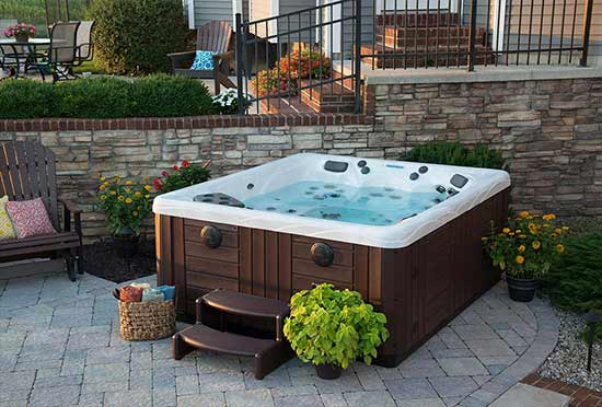 Hot tub installed on paver patio with landscaping